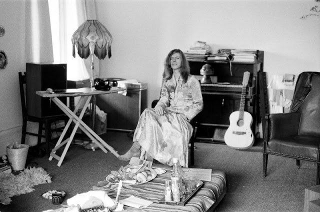 David Bowie wearing a floral-patterned dress in his house in Haddon Hall, 1971. Photo by Daily Mirror