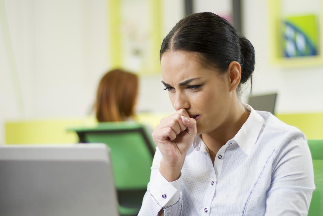 woman-at-desk-in-office-coughing